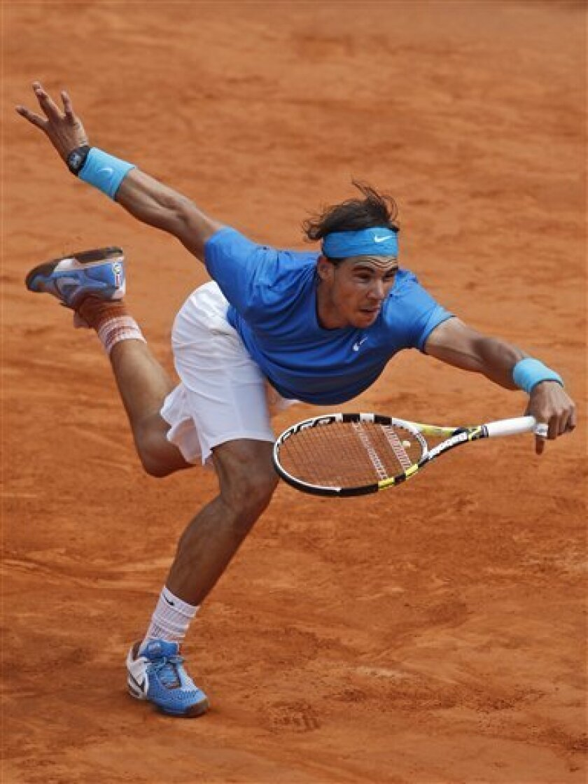 Rafael Nadal of Spain lunges forward as he tries to return against Andy Murray of Britain in the semi final match of the French Open tennis tournament in Roland Garros stadium in Paris, Friday June 3, 2011. (AP Photo/Christophe Ena)
