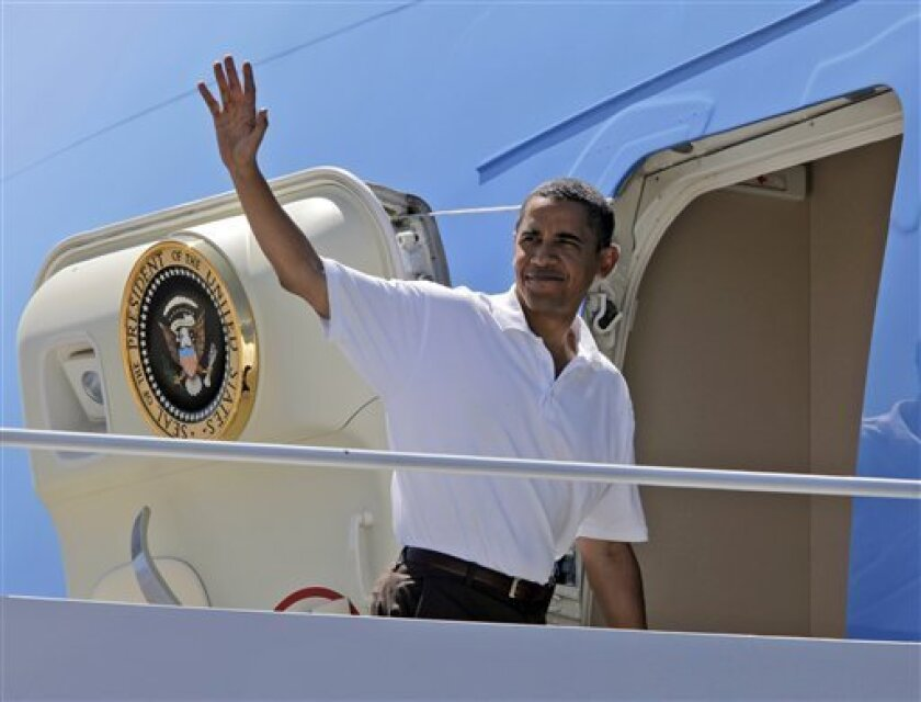 President Barack Obama waves as he boards Air Force One at Grand Canyon National Airport in Tusayan, Ariz., Sunday, Aug. 16, 2009.(AP Photo/Alex Brandon)