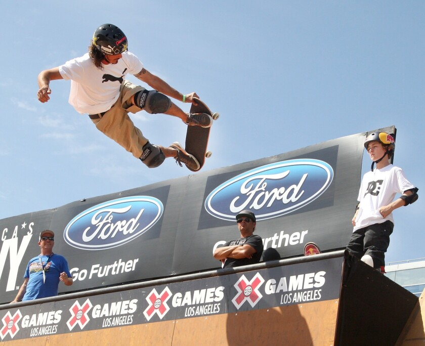 Bucky Lasek, left, competes in the X Games Skateboard Vert Final as fellow competitor Tom Schaar, 13, looks on Saturday at L.A. Live.