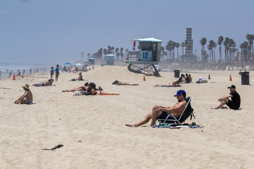 Sunbathers at Huntington Beach on Sunday flout Gov. Newsom's active-use-only order.