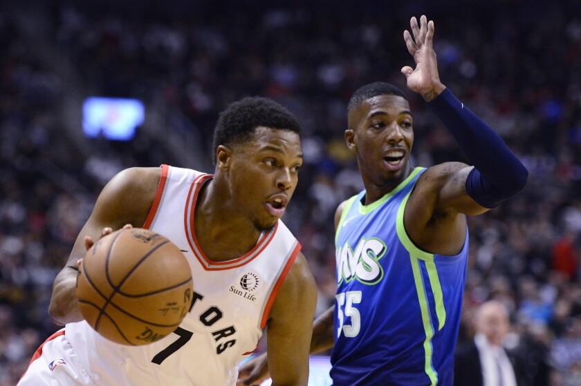 Toronto Raptors guard Kyle Lowry (7) moves past Dallas Mavericks guard Delon Wright (55) during first-half NBA basketball game action in Toronto, Sunday, Dec. 22, 2019. (Frank Gunn/The Canadian Press via AP)