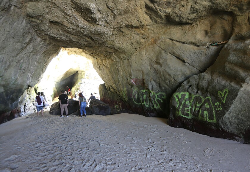 Beachgoers explore and take pictures in a sea cave at 1,000 Steps Beach in South Laguna.