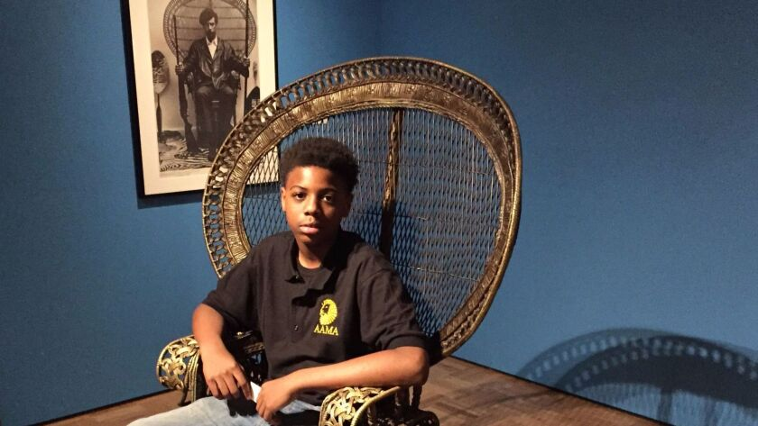 """Damion Secrease, 13, visited """"All Power to the People: Black Panthers at 50."""" He sits in a replica of the peacock chair made famous by Black Panther co-founder Huey P. Newton, shown behind him."""