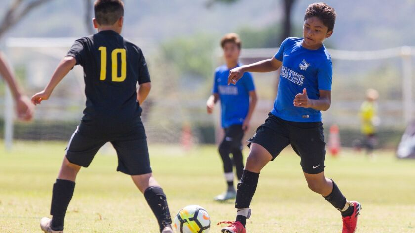 Oceanside's Damien Calleja (right) competes for control of the ball with Hawaii's Trenton Kiesel during the Surf Cup youth tournament on Saturday.