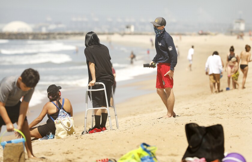 A Seal Beach lifeguard politely reminds beachgoers to keep in motion while enjoying a day at Seal Beach on Thursday.