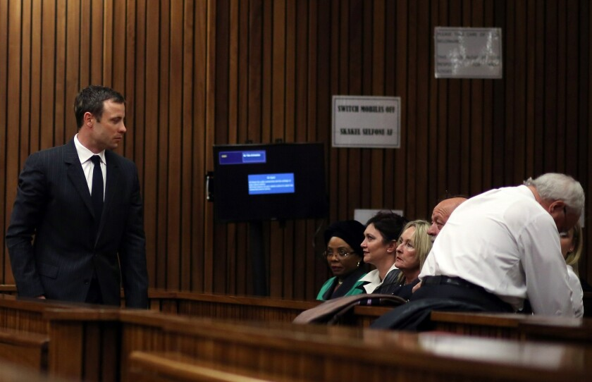South African athlete Oscar Pistorius, left, looks at June Steenkamp, third from left, and Barry Steenkamp, the parents of Reeva Steenkamp, whom Pistorius shot and killed last year.
