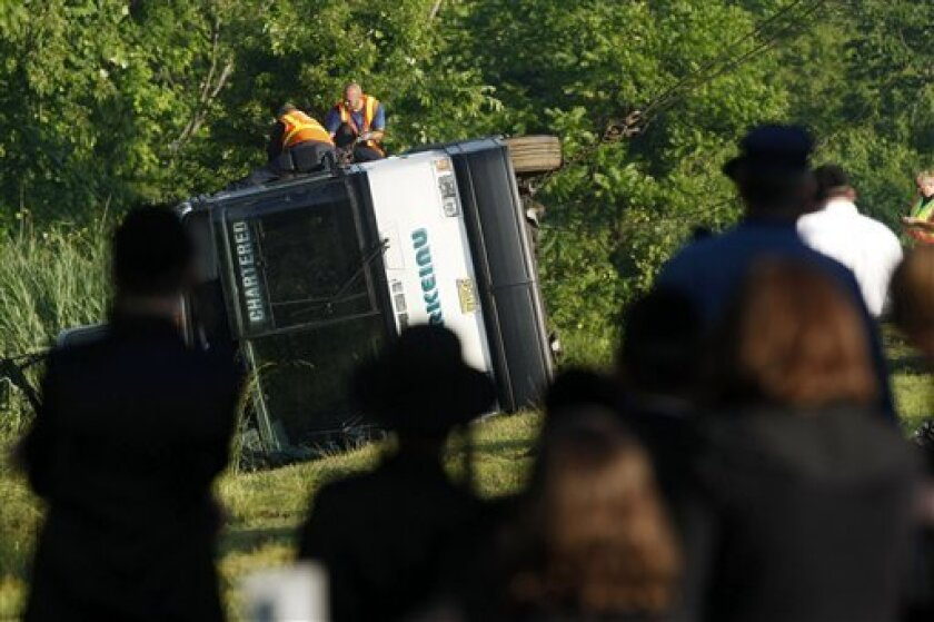 People look at an overturned bus in the woods off the Garden State Parkway near milepost 113, Wednesday, June 2, 2010, in Middletown, N.J. State police say the chartered bus carrying about 35 people ran off the parkway and flipped on its side. Sgt. Stephen Jones says some passengers sustained minor injuries. (AP Photo/Asbury Park Press, Bradley J. Penner)