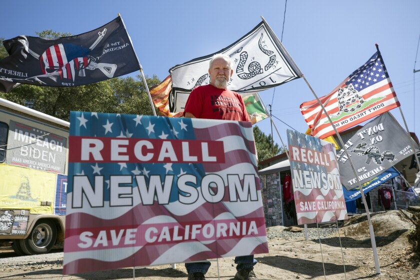 A man stands among several flags and signs, including one that says Recall Newsom, Save California