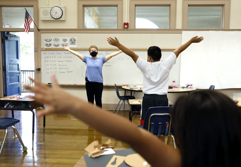 A masked teacher leads children in a stretching exercise in a classroom.
