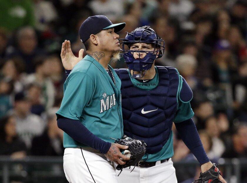 Seattle Mariners catcher Chris Iannetta, right, gives a pat to starting pitcher Felix Hernandez after a play during the third inning of a baseball game against the Minnesota Twins on Friday, May 27, 2016, in Seattle. Hernandez gave up five runs in the inning. (AP Photo/Elaine Thompson)