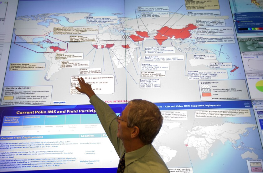 Steve Monroe, deputy director of the National Center for Emerging and Zoonotic Infectious Diseases at the U.S. Centers for Disease Control and Prevention, looks over a map showing global health issues at the agency's Emergency Operations Center in Atlanta.