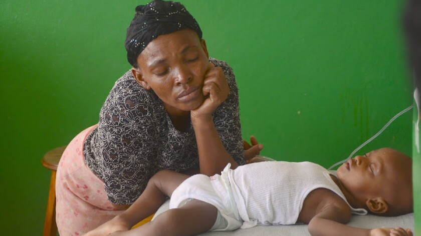 A mother keeps watch over her baby as he undergoes rehydration in the pediatric ward at St. Catherine Laboure Hospital in Port-au-Prince, Haiti, in 2014.