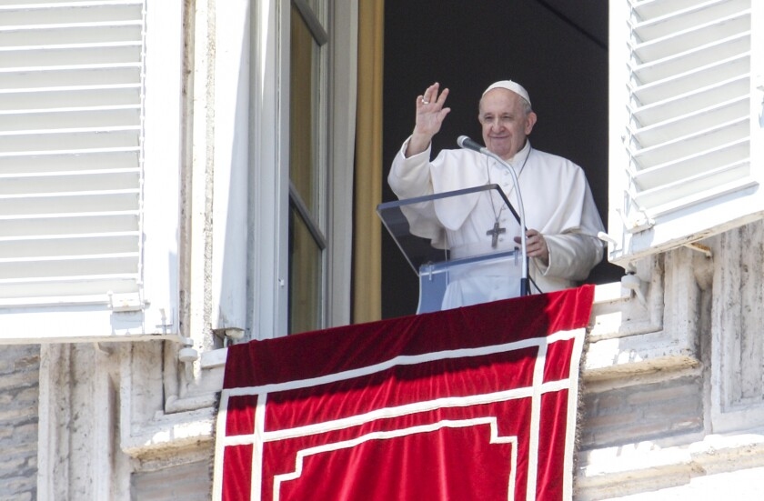 Pope Francis waves from a window with a red banner