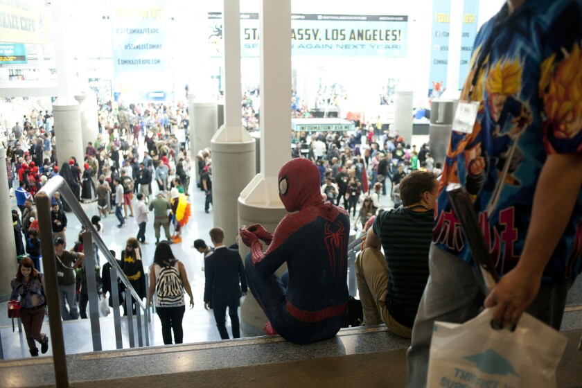 Spider-Man sits at the top of some stairs overlooking a crowd at the L.A. Convention Center.