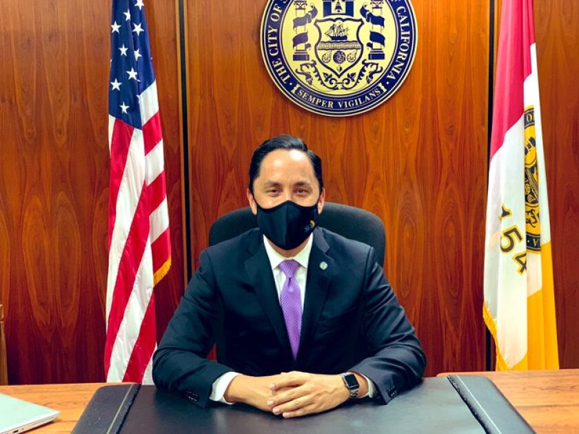 Todd Gloria, wearing his pandemic face mask, takes his place Dec. 10 as San Diego's mayor.