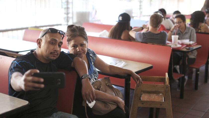 """""""I've been coming here since I was in her stomach,"""" said Rudy Ortiz, 34, says of his mother, Enedina Ortiz, 62 at Carnitas Michoacan."""