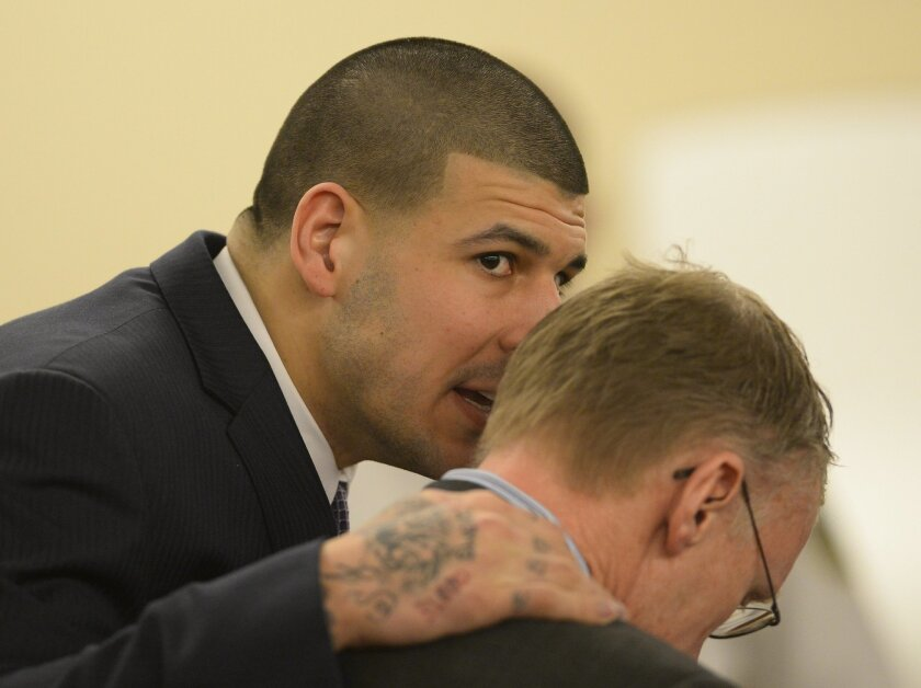 Former New England Patriots football player Aaron Hernandez talks with his attorney Charles Rankin during his murder trial at the Bristol County Superior Court in Fall River, Mass., on Friday, April 3, 2015. Hernandez is charged with killing Odin Lloyd. (AP Photo/CJ Gunther, Pool)