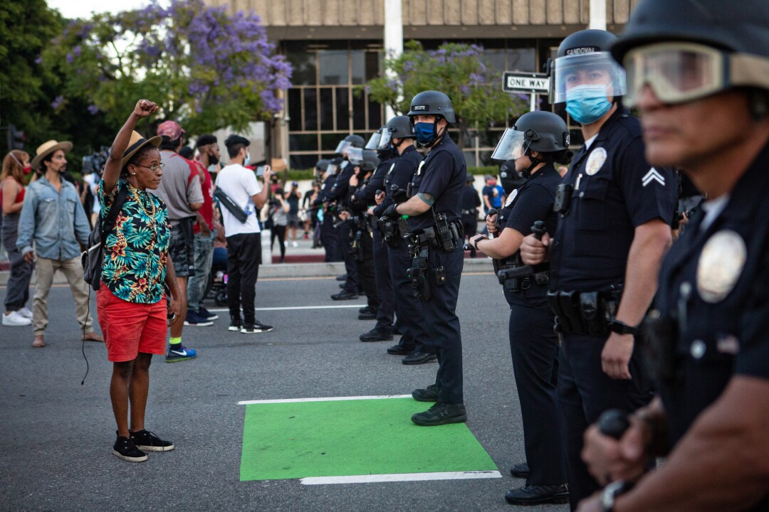 A protester confronts a line of LAPD officers in downtown Los Angeles