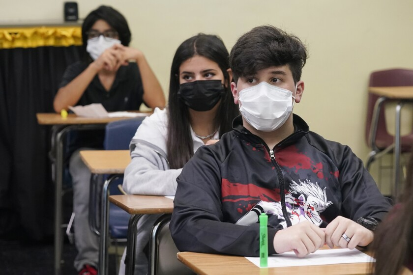 Students wearing masks sit in class