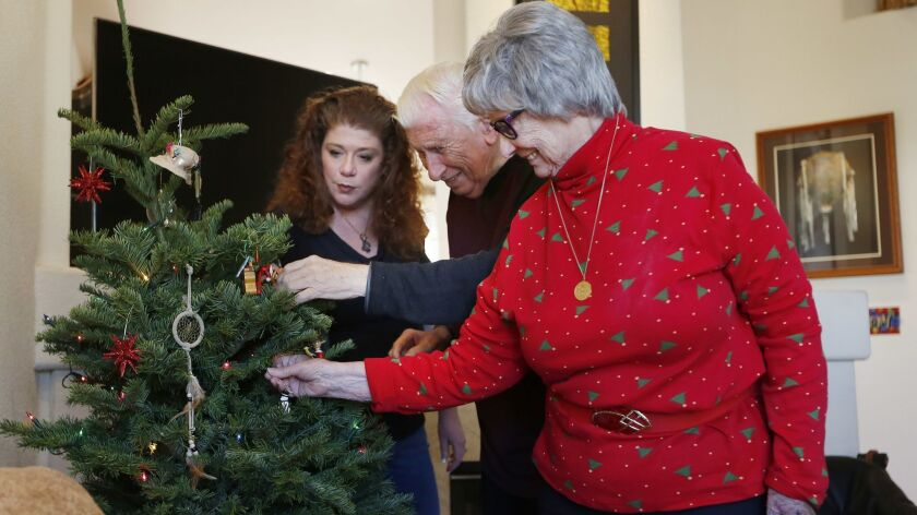 Joice Curry, left, hangs Christmas ornaments with her parents Dora and Andy Truban while visiting th