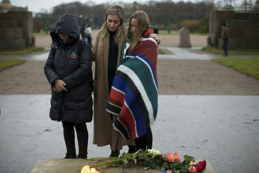 People mourn during a religious service in memory of the plane crash victims in St. Petersburg, Russia, on Wednesday, Nov. 4, 2015. A Russian official says families have identified the bodies of 33 victims killed in Saturday's plane crash over Egypt. The Russian jet crashed over the Sinai Peninsula