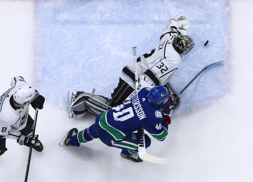 Kings goalie Jonathan Quick makes a save against Vancouver forward Elias Pettersson during an 8-2 loss to the Canucks on Wednesday.