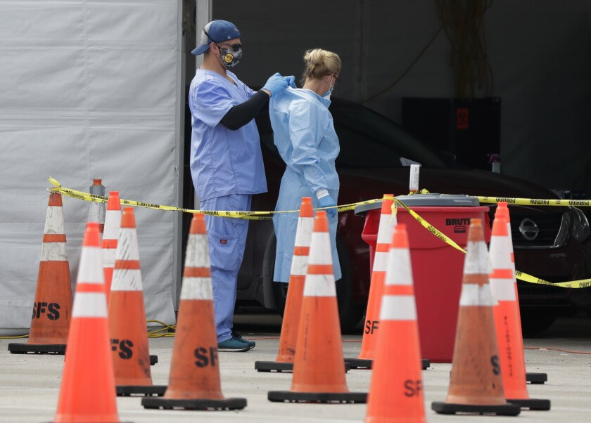 FILE - In this July 5, 2020, file photo, healthcare workers help each other with their personal protective equipment at a drive-thru coronavirus testing site outside Hard Rock Stadium in Miami Gardens, Fla. The PPE that was in dangerously short supply during the initial weeks of the coronavirus crisis in the U.S. is running out again as the virus resumes its rapid spread and the number of hospitalized patients climbs. (AP Photo/Wilfredo Lee, File)