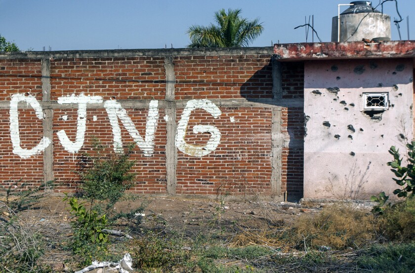 View of a bullet-riddled wall bearing the initials of Cartel Jalisco Nueva Generacion (CJNG) in Aguililla