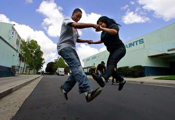 Mykel Polk, 16, and Areli Martinez, 18, practice a skateboard jump together during lunch on Saint Street, a road that cuts through the 25-acre campus. The school's disjointed layout has made it hard over the years to keep the campus free of vandalism. It also made it easier for students to ditch classes. Charter-school operator Green Dot clamped down this year with a heavy security presence and strict rules, which limited student opportunities for blowing off steam during breaks. But Green Dot has loosened up a bit, allowing skateboarding, pickup soccer games and other activities in selected areas.