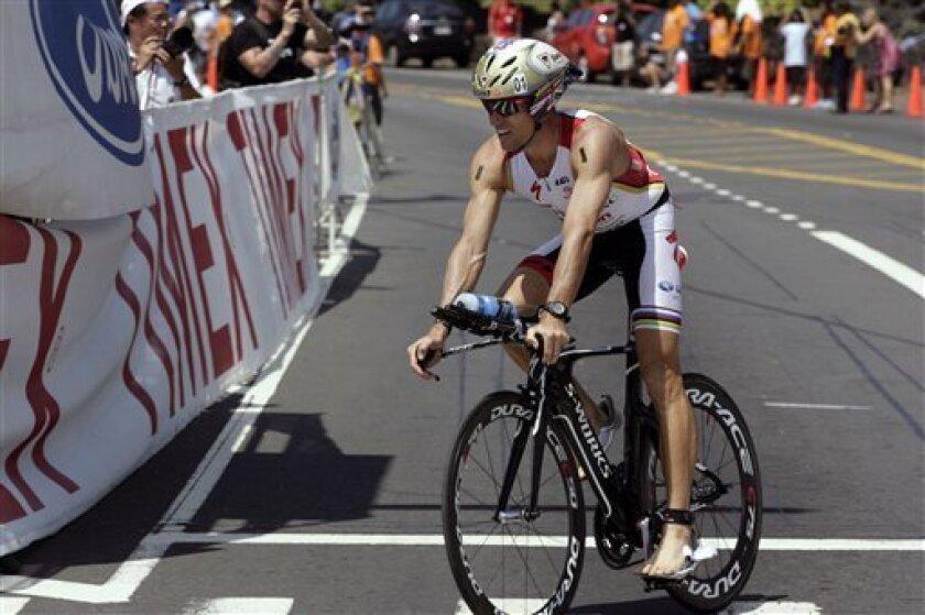 Ironman athlete Craig Alexander, of Australia, returns to Kailua-Kona, Hawaii, from a 112-mile bike ride before beginning the 26.2-mile marathon during the Ironman World Championship, Saturday, Oct. 8, 2011. (AP Photo/Chris Stewart)