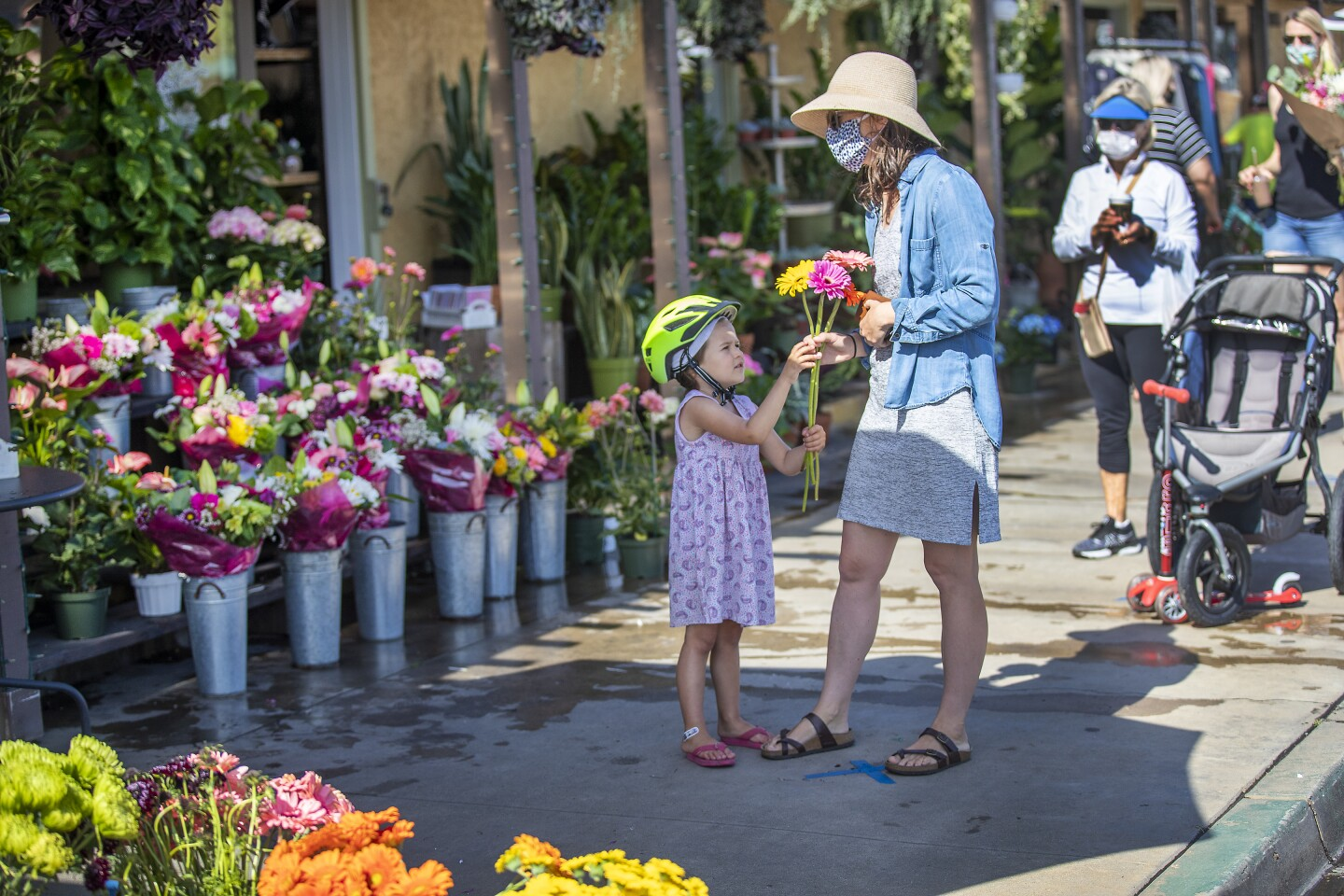 SEAL BEACH, CA -- FRIDAY, MAY 8, 2020: Christina Dagle, center, and her daughter Eleanor Eades, 4, of Seal Beach, wait in line six feet apart from others to buy flowers for a friend from Devynn's Garden in Seal Beach, CA, on May 8, 2020. Some businesses are reopening under a relaxation of the state's stay at home order. Bookstores, music stores, toy stores, florists, sporting goods retailers, clothing stores and others can reopen for pickup and curbside service. (Allen J. Schaben / Los Angeles Times)