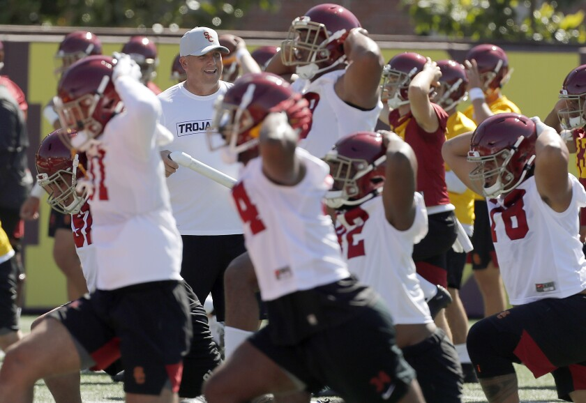 USC football coach Clay Helton runs players through warm-ups during the opening of training camp at USC.
