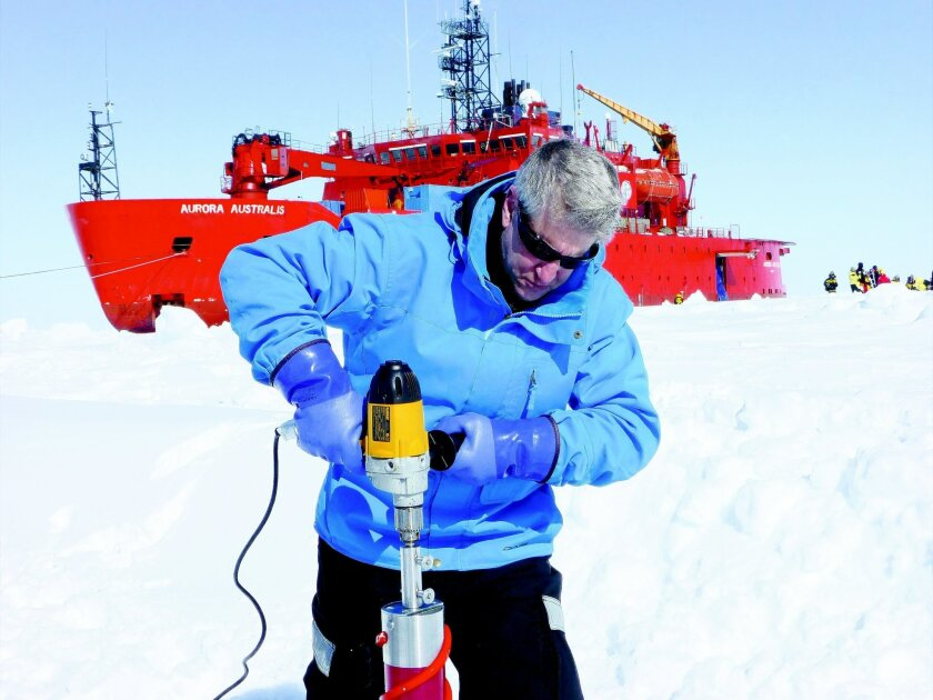 University of Utah mathematician Ken Golden drills holes in ice to test its permeability, in front of the Aurora Australis. By Christian Sampson