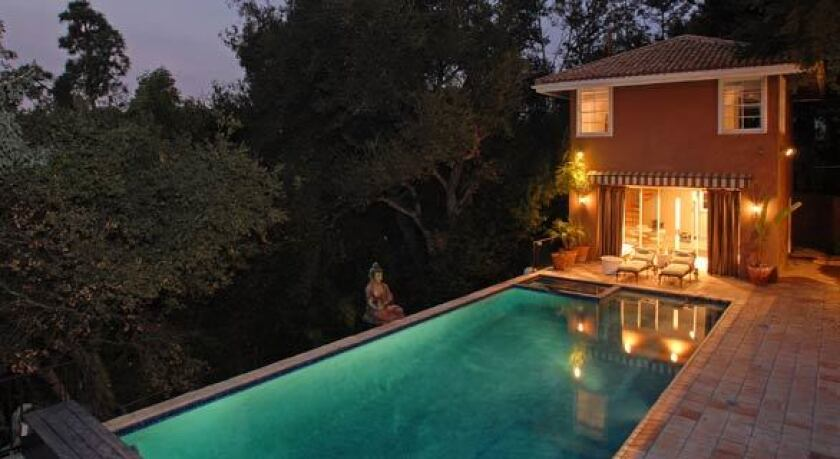 A two-story guesthouse stands next to the swimming pool at Ashlee Simpson's house.