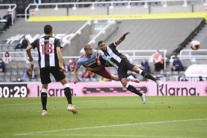 West Ham's Tomas Soucek, left, and Newcastle's Jamaal Lascelles challenge for the ball during the English Premier League soccer match between Newcastle United and West Ham United at St. James' Park in Newcastle, England, Sunday, July 5, 2020. (Laurence Griffiths/Pool via AP)