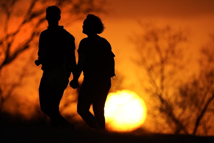 En esta imagen de archivo, tomada el 10 de marzo de 2021, una pareja camina por un parque