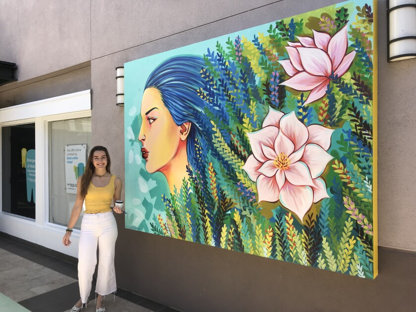 Marina Alberti with a mural she recently completed at Flower Hill Promenade.