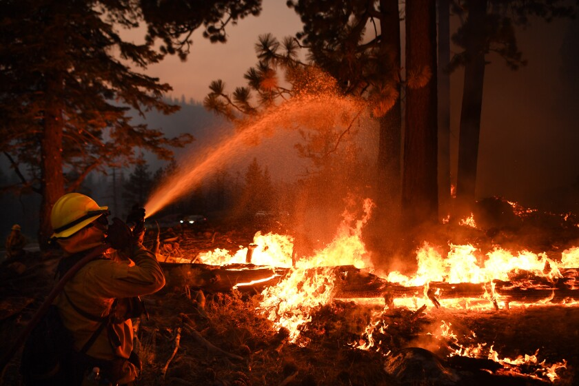 Firefighters battle battle the Caldor fire along highway 89 west of Lake Tahoe.