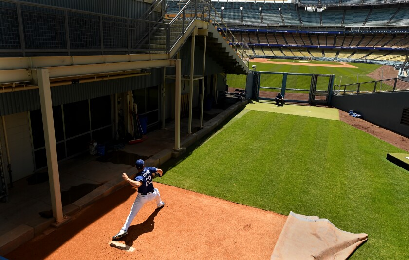 Dodgers starting pitcher Clayton Kershaw throws a pitch in the bullpen during a workout