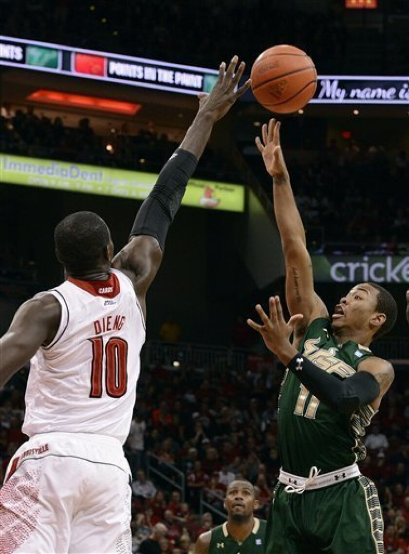 South Florida's Anthony Collins, right, gets a shot off over Louisville's Gorgui Dieng during the first half of an NCAA college basketball game Saturday Jan. 12, 2013, in Louisville, Ky. (AP Photo/Timothy D. Easley)