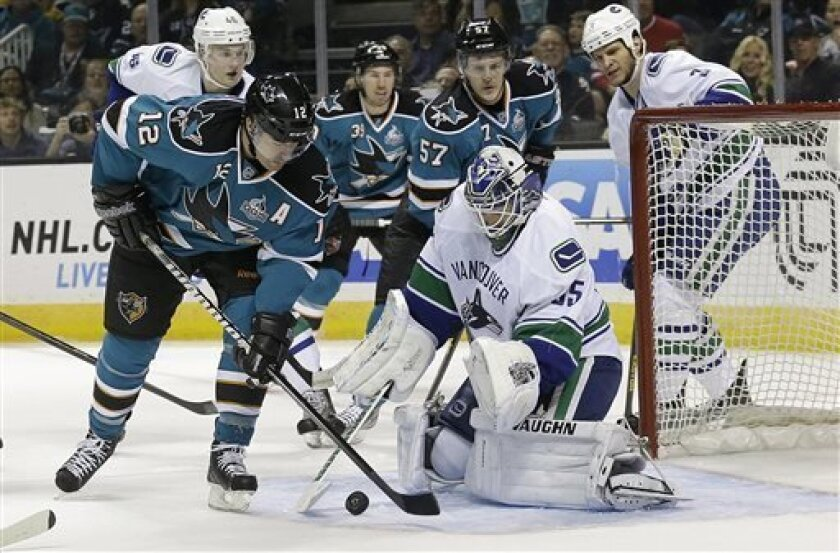 Vancouver Canucks goalie Cory Schneider (35) defends the goal as San Jose Sharks center Patrick Marleau (12) shoots during the first period of an NHL hockey game in San Jose, Calif., Monday, April 1, 2013. (AP Photo/Jeff Chiu)
