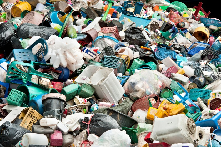 A large pile of plastic waste is shown, including bottles, chairs and containers.