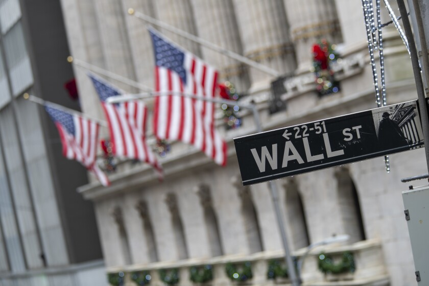 A Wall Street street sign is framed by American flags outside the New York Stock Exchange