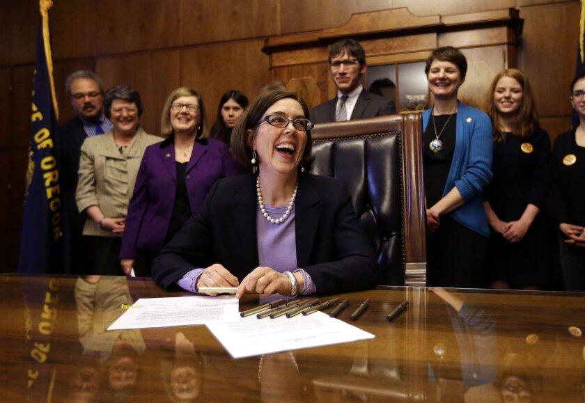 Oregon Gov. Kate Brown signs a voter registration bill.