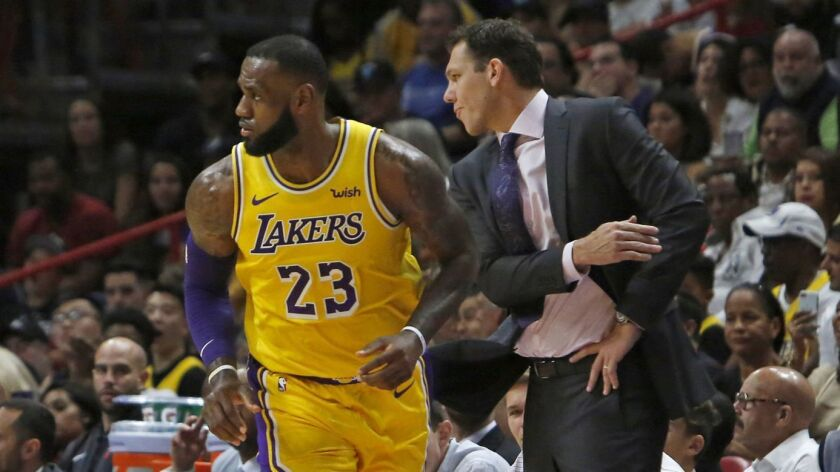Lakers forward LeBron James is congratulated by coach Luke Walton after scoring against the Heat during the first quarter Sunday.