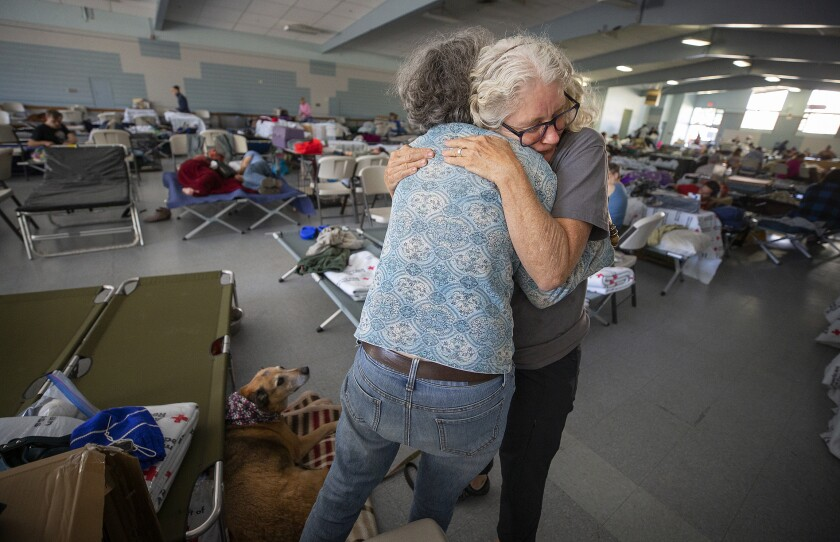 Volunteer Barbara Wood gives a hug to a Kincade fire evacuee at a Red Cross shelter at the Sonoma County Fairgrounds in Santa Rosa, Calif.