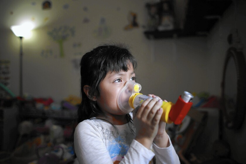 Four-year-old Alani Hernandez, whose family lives in Fontana, is so used to the variety of devices she uses for her asthma that she refers to them as if they were toys. She calls this one a teddy bear.