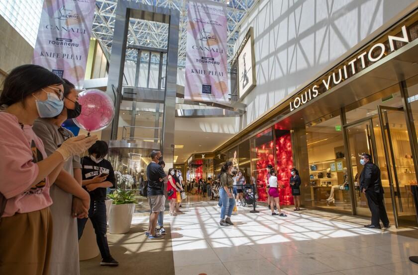 Shoppers follow social-distancing etiquette outside a Louis Vuitton store at South Coast Plaza on June 11.