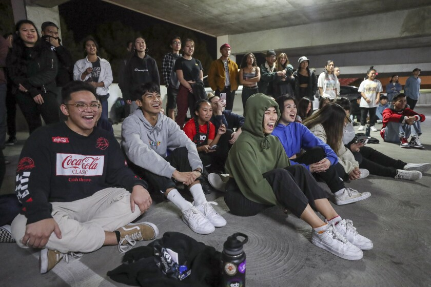 Fellow dancers cheer and applaud as a hip-hop dance group performs during the end of the year choreography project put on by the SDSU Vietnamese Student Organization Modern, a collegiate hip-hop dance troupe, in a parking garage on the SDSU campus on Thursday, December 5, 2019 in San Diego, California.