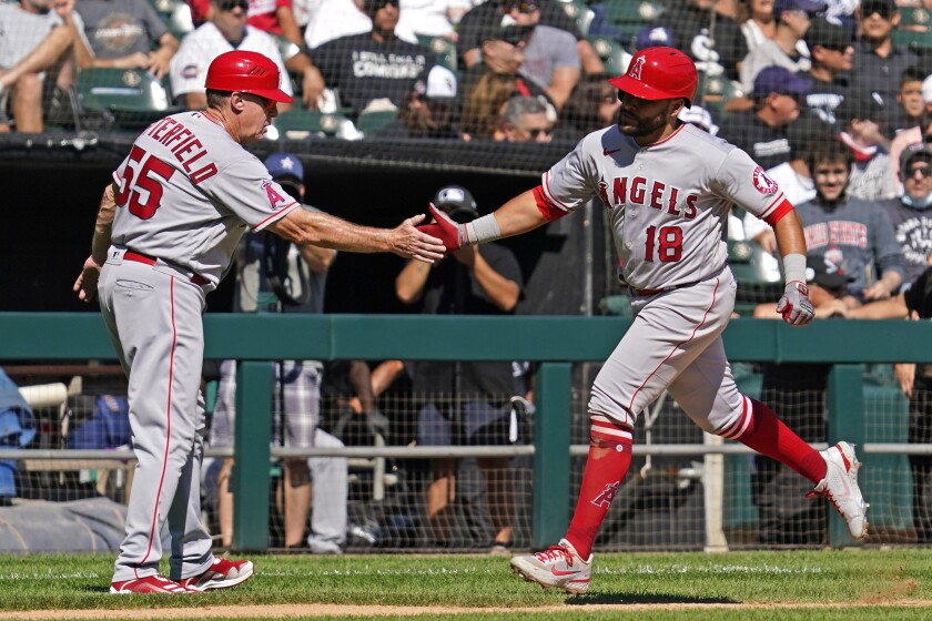 Los Angeles Angels' Jose Rojas, right, celebrates with third base coach Brian Butterfield after hitting a two-run home run during the fourth inning of a baseball game against the Chicago White Sox in Chicago, Thursday, Sept. 16, 2021. (AP Photo/Nam Y. Huh)